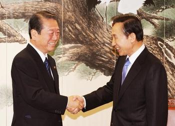 握手を交わす小沢代表(左)と李次期大統領(共同取材団撮影)=21日、ソウル(聯合).jpg